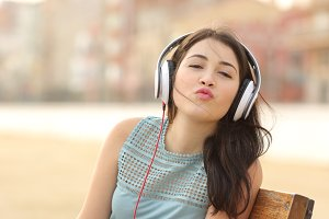 Teenager girl with headphones kissing at camera.jpg