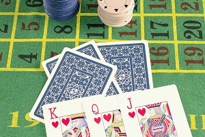 Poker cards with chips on green carp