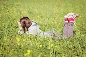Teen girl down on meadow