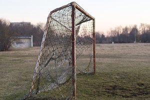 Old rusty soccer goal on sunset