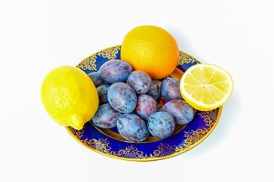 Plums, lemons and oranges on a plate