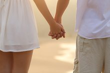 Close up of a couple walking and holding hands on the beach.jpg