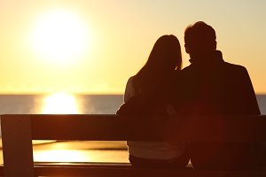Back view of a couple watching sun on the beach.jpg