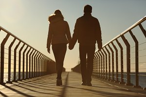 Back silhouette of a couple walking holding hands.jpg