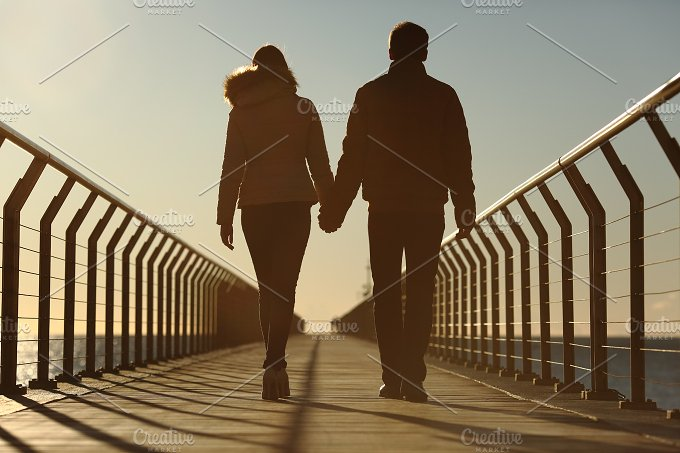 Back silhouette of a couple walking holding hands.jpg - People