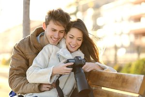 Couple of tourists reviewing photos in a dslr camera.jpg