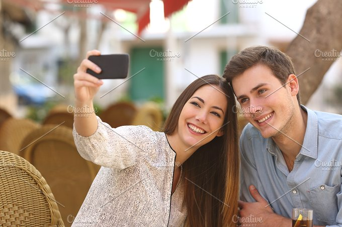 Couple taking a selfie photo in a restaurant.jpg - Technology