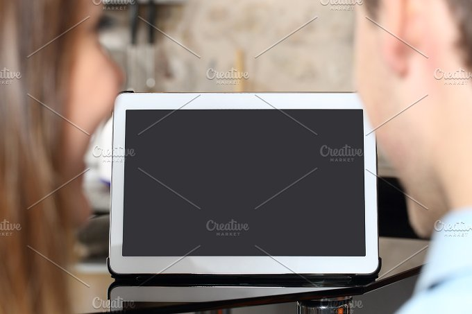 Couple watching and showing a blank tablet screen.jpg - Technology