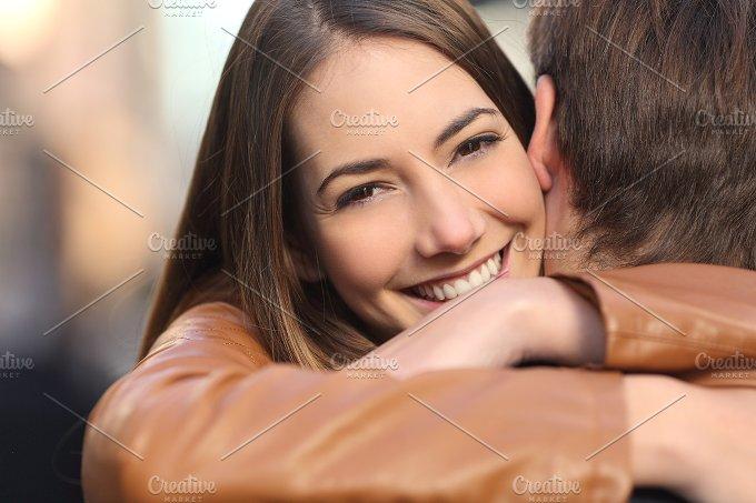 Happy girlfriend hugging her boyfriend and looking at camera.jpg - People