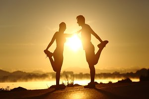 Silhouette of a fitness couple stretching at sunset.jpg