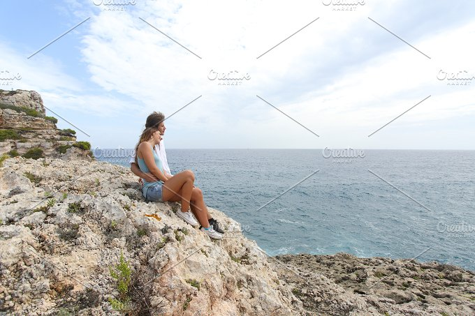 Teenager couple looking at horizon on a cliff.jpg - Holidays