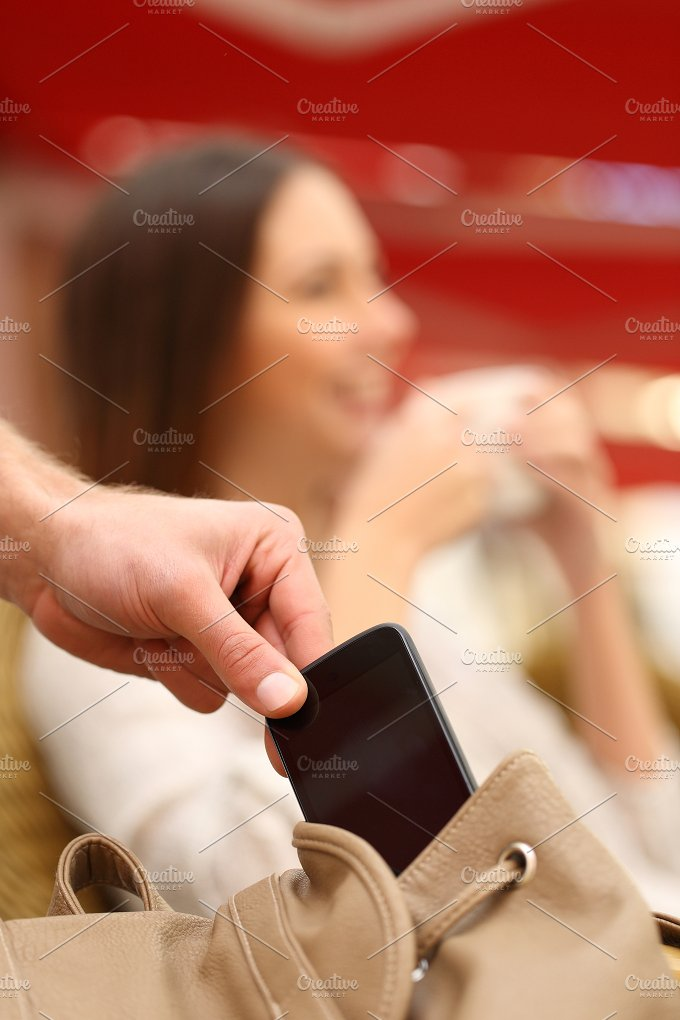 Thief stealing a mobile phone from a woman bag.jpg - People