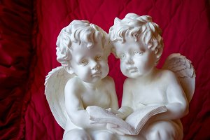 Two angels reading a book