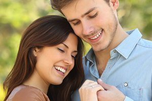 Couple hugging while looks a engagement ring.jpg
