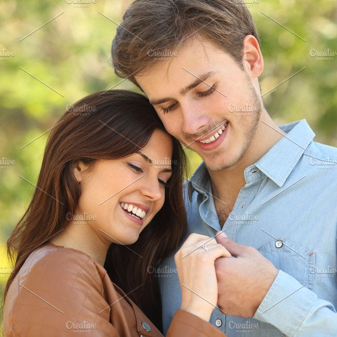 Couple hugging while looks a engagement ring.jpg - People