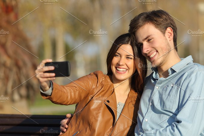 Couple taking selfie photo sitting in a bench.jpg - Technology