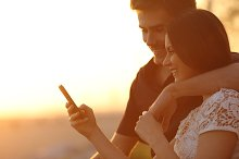 Couple using a smartphone in a sunset back light.jpg
