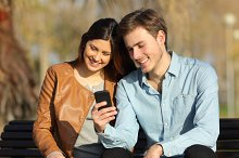 Couple watching a smart phone sitting in a bench.jpg