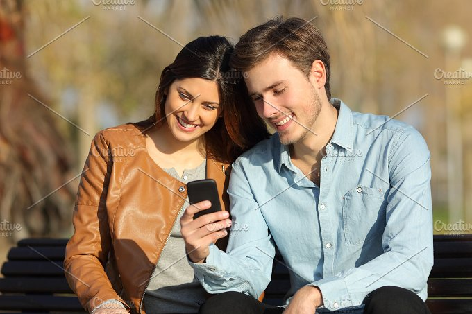 Couple watching a smart phone sitting in a bench.jpg - Technology