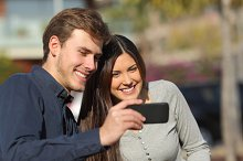 Happy couple watching media in a smart phone outdoors.jpg