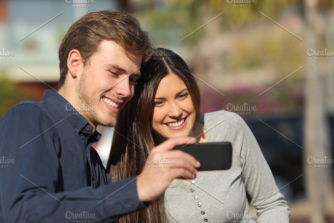 Happy couple watching media in a smart phone outdoors.jpg - Technology