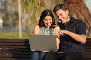 Couple watching media in a laptop sitting in a bench.jpg
