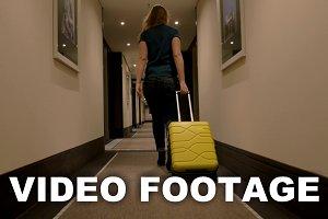 Woman Walking along Hotel Passage