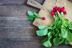 Fresh radishes on old wooden table