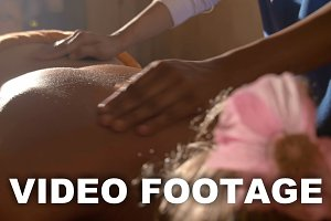 Woman under hot stone back massage