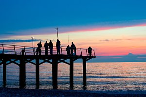 Fishermen on a pier at sunset