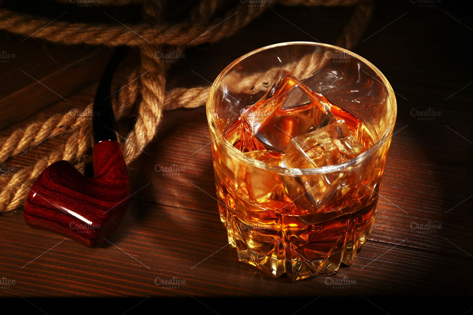 Glass with whiskey, ice cubes and