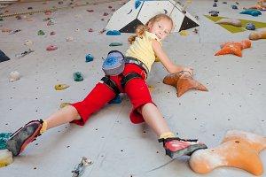 Little girl climbing on rockwall
