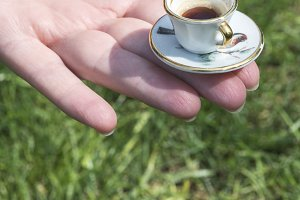 Hand hold very small cup of coffee