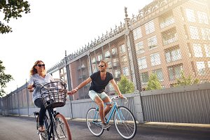 Couple holding hands and riding bike