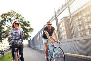 Young couple cycling in an urban par