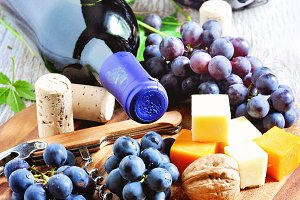 Bottle of red wine, grapes, cheese