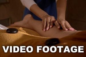 Massaging Leg with Hot Stones