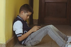 child at home with mobile phone