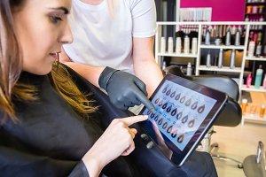 Woman looking hair dye on tablet