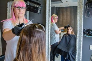 Woman looks in mirror to hairdresser