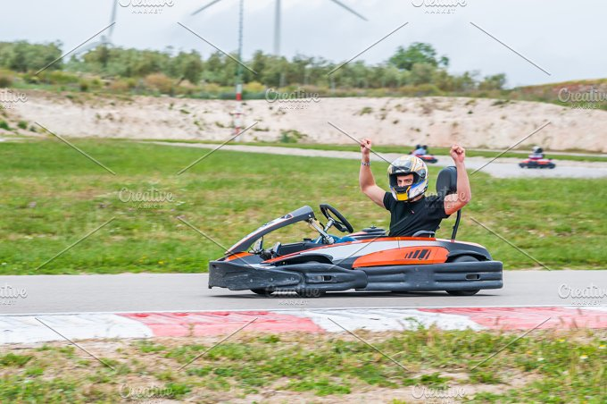 Man with arms up driving a kart. Win - Sports