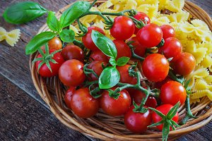 fresh organic cherry tomatoes and paste with basil garlic on a dark background