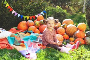 Little cute girl and pumpkins