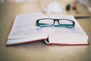 Open book and black glasses