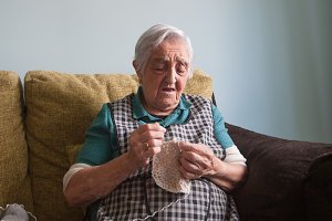 Elderly woman sewing at home.