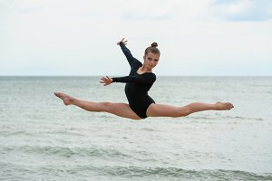 Gymnast Dancer Jumping On The Sea Be