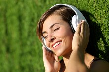 Happy girl listening to the music with headphones in a park.jpg