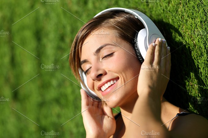 Happy girl listening to the music with headphones in a park.jpg - Technology