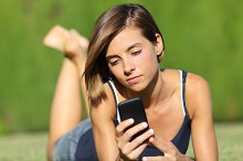 Pretty teenager girl holding a smart phone lying on the grass.jpg