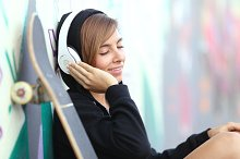 Skater teen girl listening to the music with headphones.jpg